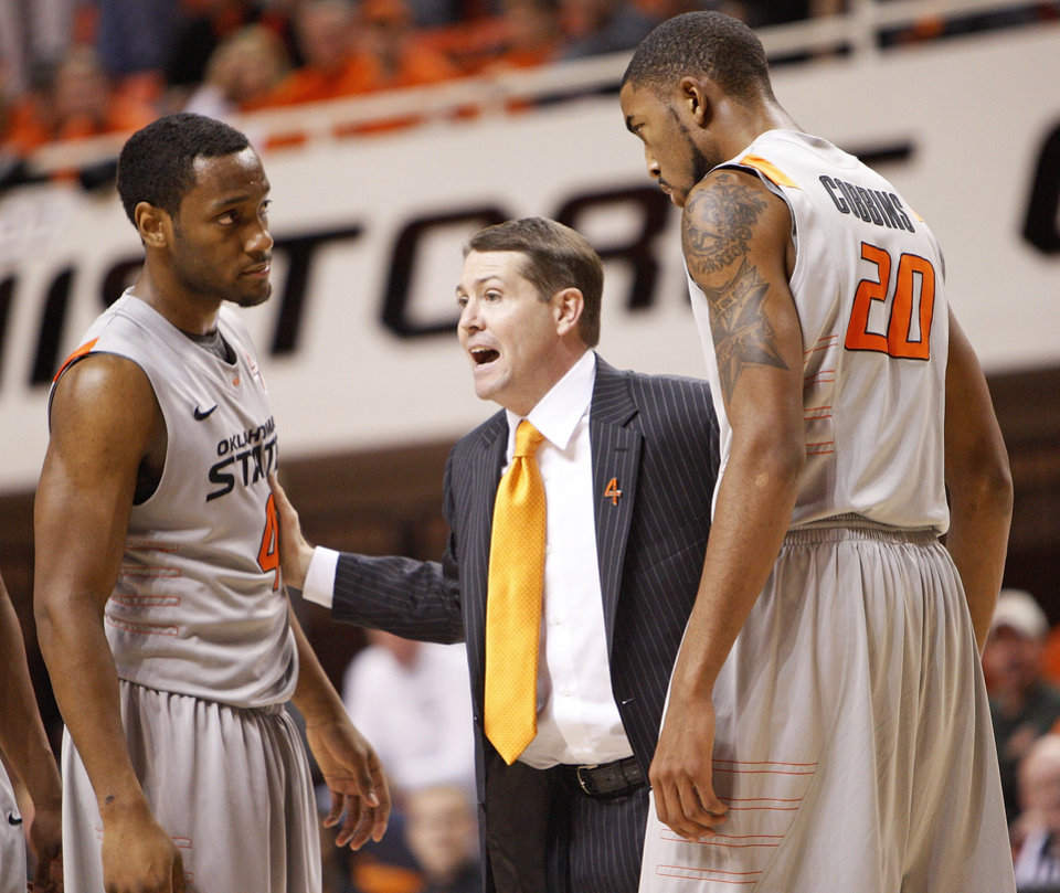 Photo - OSU head coach Travis Ford talks to Brian Williams (4) and Michael Cobbins (20) in the second half of a men's college basketball game between the Oklahoma State University Cowboys and the Texas Tech University Red Raiders at Gallagher-Iba Arena in Stillwater, Okla., Wednesday, Jan. 4, 2012. OSU won, 67-59. Photo by Nate Billings, The Oklahoman