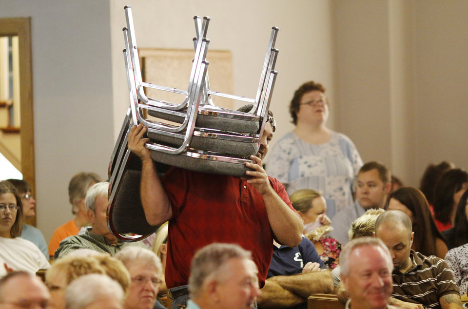 Photo - A volunteer carries more chairs into the sanctuary for the last service at First Baptist Church of El Reno Sunday, September 8, 2013. Photo by Doug Hoke, The Oklahoman