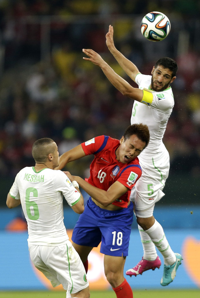Photo - South Korea's Kim Shin-wook, centre, is challenged by Algeria's Rafik Halliche, rear, and Algeria's Djamel Mesbah during the group H World Cup soccer match between South Korea and Algeria at the Estadio Beira-Rio in Porto Alegre, Brazil, Sunday, June 22, 2014. (AP Photo/Fernando Vergara)
