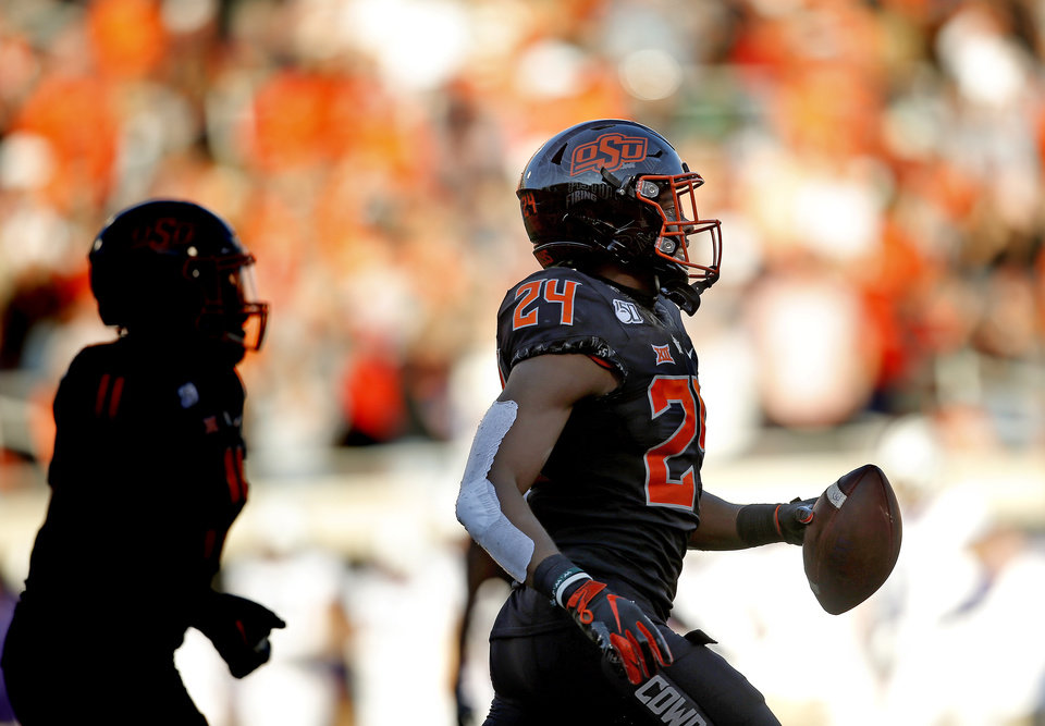 Photo - Oklahoma State's Jarrick Bernard (24) celebrates an interception in the third quarter during the college football game between the Oklahoma State University Cowboys and the TCU Horned Frogs at Boone Pickens Stadium in Stillwater, Okla.,  Saturday, Nov. 2, 2019. OSU won 34-27. [Sarah Phipps/The Oklahoman]