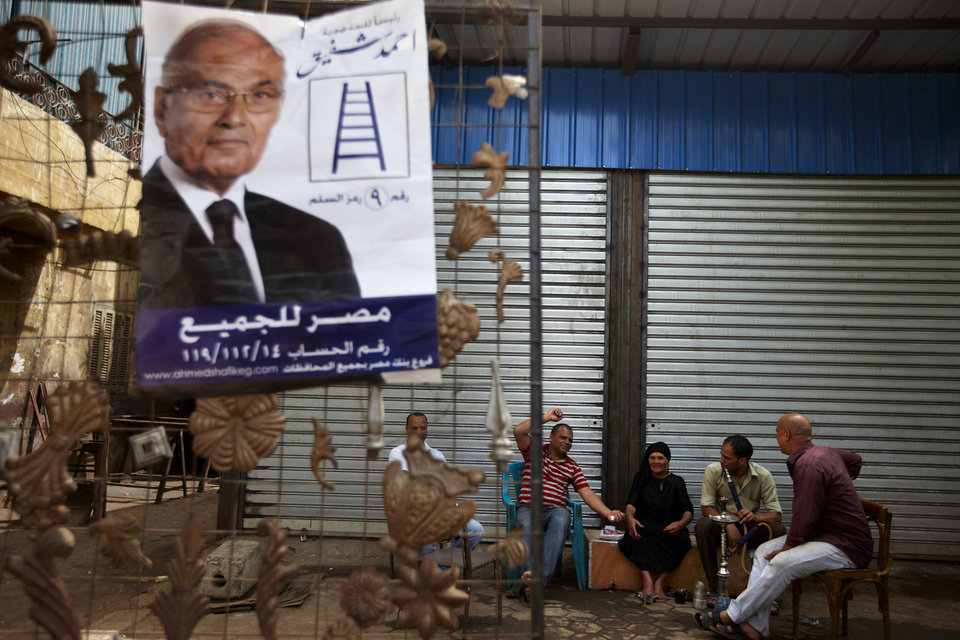 Photo -   Egyptians sit at a coffee shop near a poster of Egyptian presidential candidate Ahmed Shafiq with Arabic that reads,