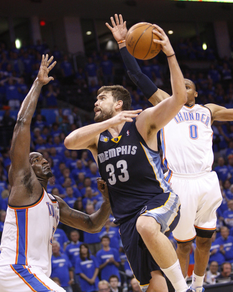 Photo - Memphis Grizzlies center Marc Gasol, of Spain, shoots between Oklahoma City Thunder center Kendrick Perkins, left, and guard Russell Westbrook, right, in the fourth quarter of Game 2 of a second-round NBA basketball playoff series in Oklahoma City, Tuesday, May 3, 2011. Oklahoma City won 111-102. (AP Photo/Sue Ogrocki)