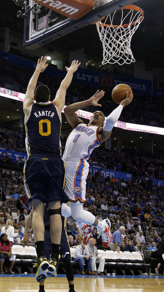 Photo - Oklahoma City 's Russell Westbrook (0) shoots a lay up as Utah's Enes Kanter (0) defends during the NBA game between the Oklahoma City Thunder and the Utah Jazz at the Chesapeake Energy Arena, Sunday, March 30, 2014, in Oklahoma City. Photo by Sarah Phipps, The Oklahoman