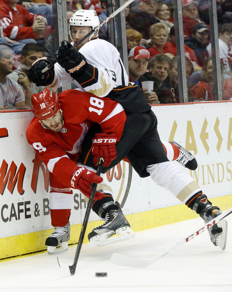 Photo - Anaheim Ducks center Nick Bonino (13) hits Detroit Red Wings defenseman Ian White (18) into the boards to gain control of the puck in the first period of an NHL hockey game on Friday, Feb. 15, 2013, in Detroit. (AP Photo/Duane Burleson)