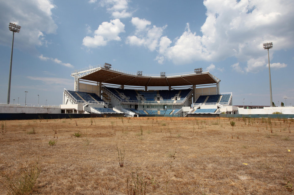 Photo - FILE - In this Thursday, Aug. 2, 2012, file photo, weeds sprout in the remains of what was once the playing field at the abandoned Olympic softball venue in southern Athens. The legacy of Athens' Olympics has stirred vigorous debate, and Greek authorities have been widely criticized for not having a post-Games plan for the infrastructure. While some of the venues built specifically for the games have been converted for other uses, many are underused or abandoned, and very few provide the state with any revenue. Some critics even say that the multibillion dollar cost of the games played a modest role in the nation's 2008 economic meltdown. (AP Photo/Thanassis Stavrakis)