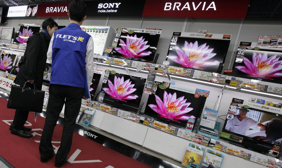 Photo -   In this March 2, 2012 photo, a visitor inspects Sony's flat panel TVs at a retail store in Tokyo. Sony Corp. now has a new president - Kazuo Hirai, the former head of its game division. But shareholders are already raising doubts about his ability to revive the Japanese electronics and entertainment giant. (AP Photo/Koji Sasahara)