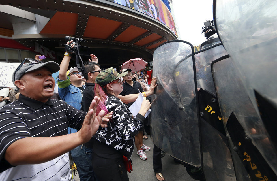 Photo - Anti-coup protesters push Thai soldiers who move in to disperse them outside a shopping complex in Bangkok, Thailand Saturday, May 24, 2014. Thailand's coup leaders said Saturday they will keep former Prime Minister Yingluck Shinawatra, Cabinet members and anti-government protest leaders detained for up to a week to give them