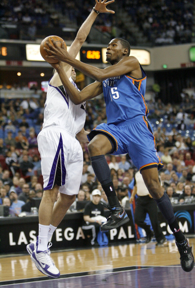 Photo - Oklahoma City Thunder forward Kevin Durant, right, drives to the basket against Sacramento Kings defender Francisco Garcia during the first half of an NBA basketball game in Sacramento, Calif., Sunday, March 7, 2010. (AP Photo/Steve Yeater) ORG XMIT: SCA101