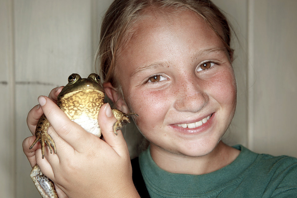 Kylie Moates, 9, smiles with her bullfrog.
