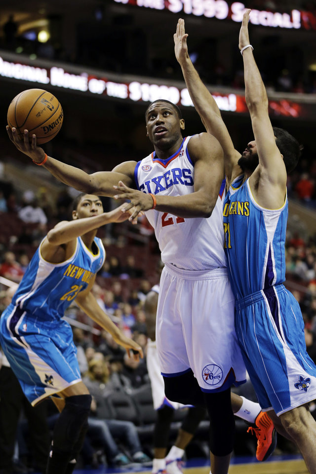 Photo - Philadelphia 76ers' Thaddeus Young, center, drives to the basket between New Orleans Hornets' Greivis Vasquez, right, of Venezuela, and Anthony Davis (23) during the first half of an NBA basketball game, Tuesday, Jan. 15, 2013, in Philadelphia. (AP Photo/Matt Slocum)