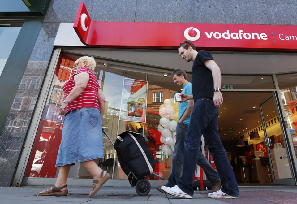 Photo - People walk past a Vodafone shop in London, on Friday, June 6, 2014. Vodafone, one of the world's largest cellphone companies, revealed the scope of government snooping into phone networks Friday, saying authorities in some countries are able to directly access an operator's network without seeking permission. The company outlined the details in a report that is described as the first of its kind, covering 29 countries in which it directly operates. It gives the most comprehensive look to date on how governments monitor the communications of their citizens. (AP Photo/Lefteris Pitarakis)