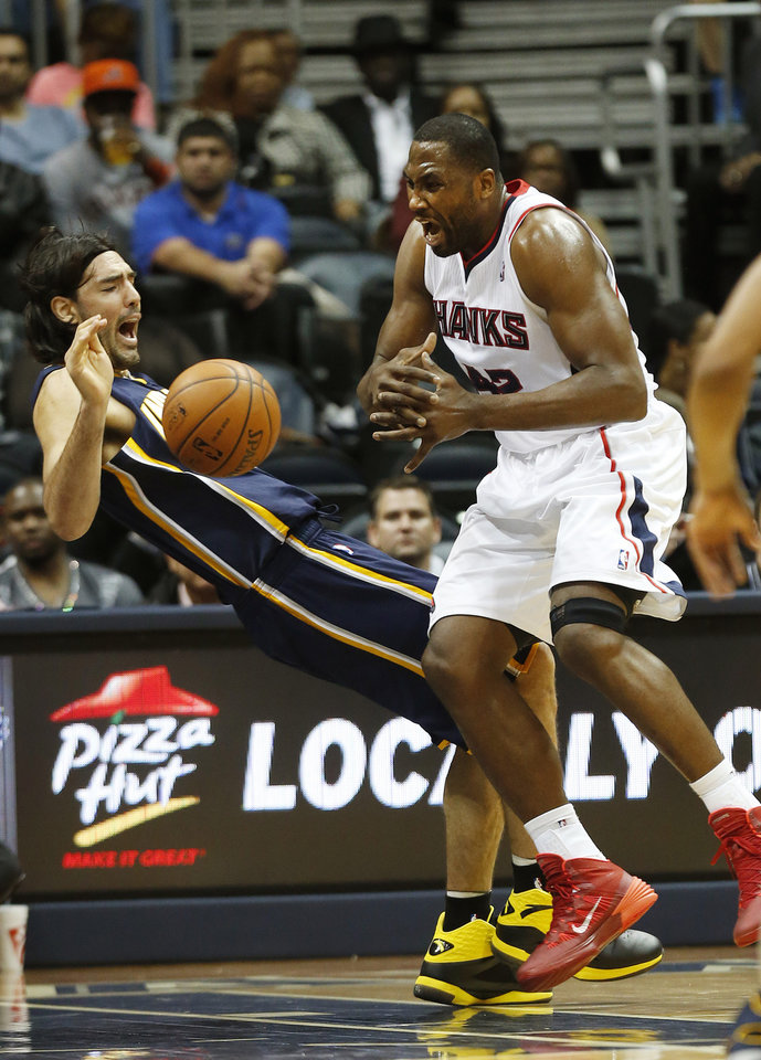 Photo - Atlanta Hawks power forward Elton Brand (42) collides with Indiana Pacers power forward Luis Scola (4) in the first  half of an NBA basketball game, Tuesday, Feb. 4, 2014, in Atlanta. Brand was called for an offensive foul. (AP Photo/John Bazemore)