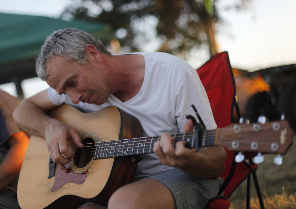 Photo - Jay Martin, of Oklahoma City, plays guitar near his camp during the Woody Guthrie Folk Festival in Okemah, Okla., Thursday, July 12, 2012.  Photo by Garett Fisbeck, The Oklahoman