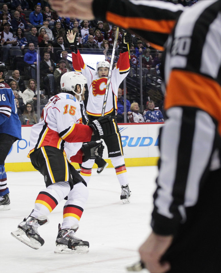 Photo - Calgary Flames center Joe Colborne (8) celebrates his goal against the Colorado Avalanche in the second period of an NHL game in Denver on Monday, Jan. 6, 2014. Calgary Flames right wing Kevin Westgarth (15) skates toward Colborne. (AP Photo/Joe Mahoney)
