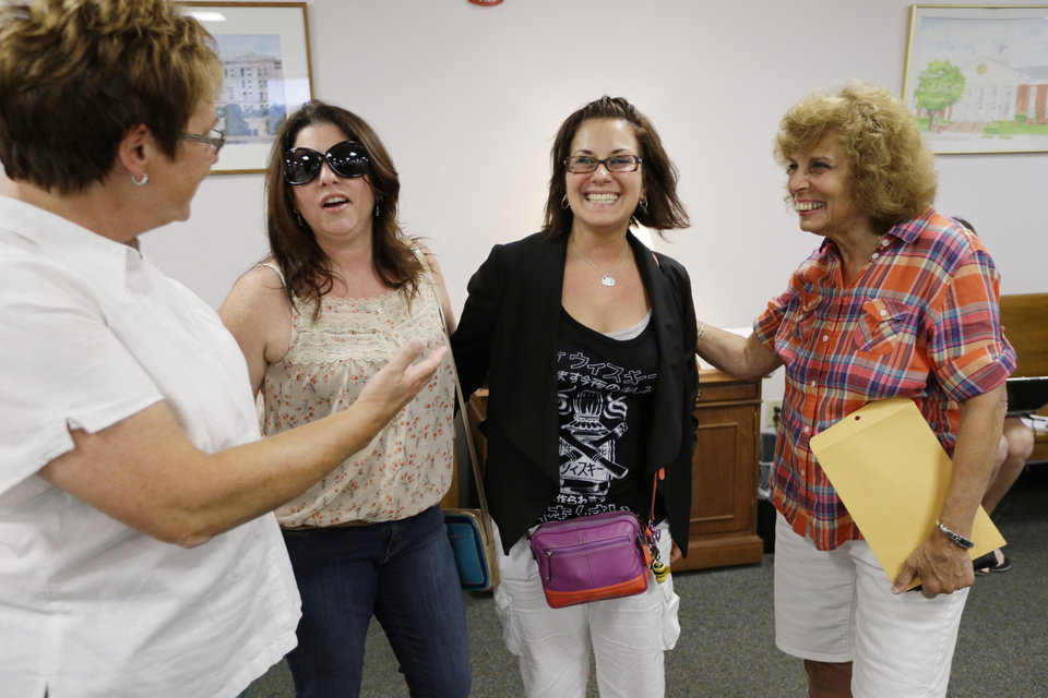 Ellen Toplin, left, and Charlene Kurland, right, who obtained a marriage license at a Montgomery County office despite a state law banning such unions, meet with Nicola Cucinotta, center left, and Tamara Davis before they get their license, Wednesday, July 24, 2013, in Norristown, Pa. Five same-sex couples have obtained marriage licenses in the suburban Philadelphia county that is defying a state ban on such unions. (AP Photo/Matt Rourke)