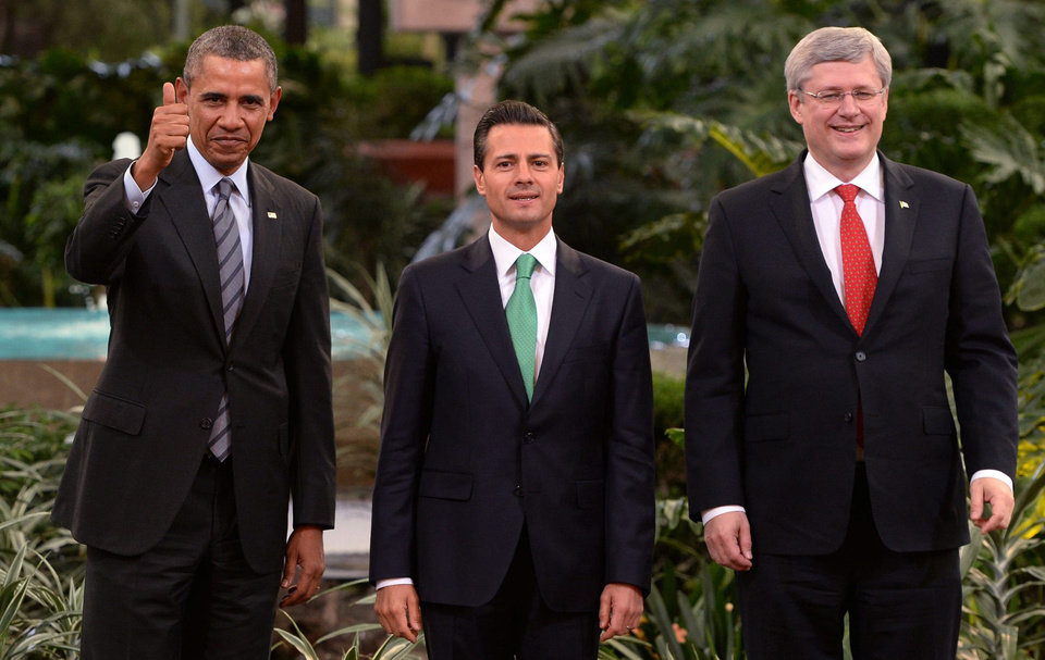 Photo - President Barack Obama, left, gives a thumbs up as he poses for photos with Mexico's President Enrique Pena Nieto, center, and Canada's Prime Minister Stephen Harper at the North American Leaders Summit in Toluca, Mexico, Wednesday, Feb. 19, 2014. The leaders met in part to highlight the economic cooperation that has grown since the North American Free Trade Agreement (NAFTA) joined the U.S., Canada and Mexico 20 years ago.  (AP Photo/Canadian Press, Sean Kilpatrick)