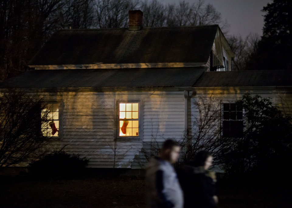 A Christmas stocking hangs in the window of a home as mourners return from visiting a memorial to the victims of the Sandy Hook Elementary School shooting down the road from the school's entrance, Monday, Dec. 17, 2012, in Newtown, Conn. (AP Photo/David Goldman) ORG XMIT: CTDG124