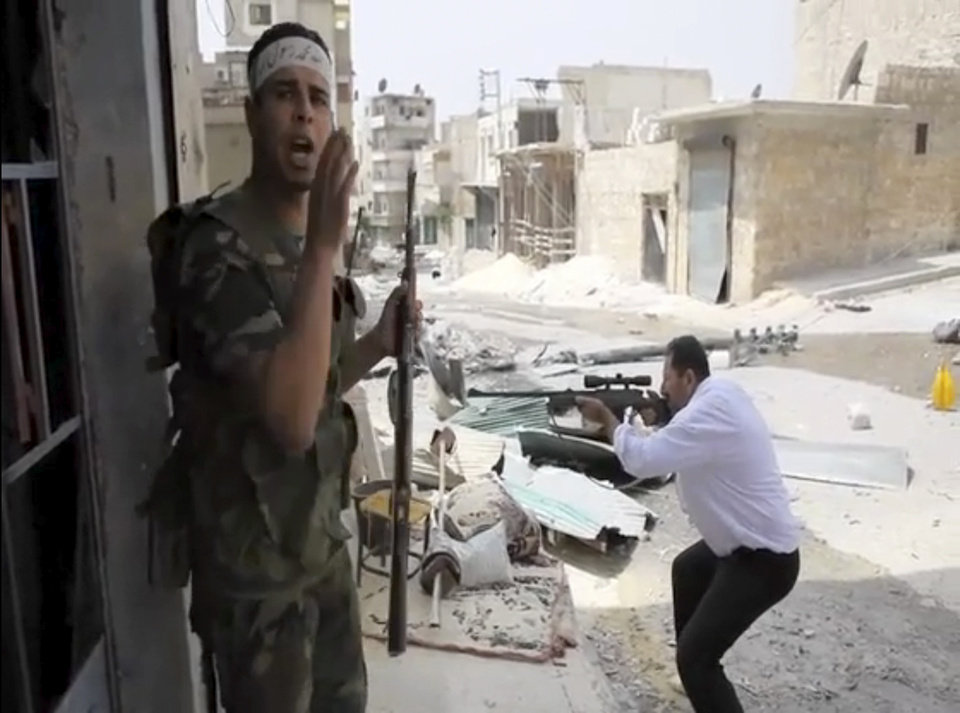 Photo -   In this image made from video and accessed Saturday, Sept. 1, 2012, a Free Syrian Army fighter calls out to comrades as another fighter fires at Syrian Army positions in Aleppo, Syria. Syrian troops bombarded the northern city of Aleppo Saturday with warplanes and mortar shells as soldiers clashed with rebels in different parts of Syria's largest city, activists said. The Britain-based Syrian Observatory for Human Rights said the clashes were concentrated in several tense neighborhoods where some buildings were damaged and a number of people were wounded. (AP Photo/Robert King via AP video)