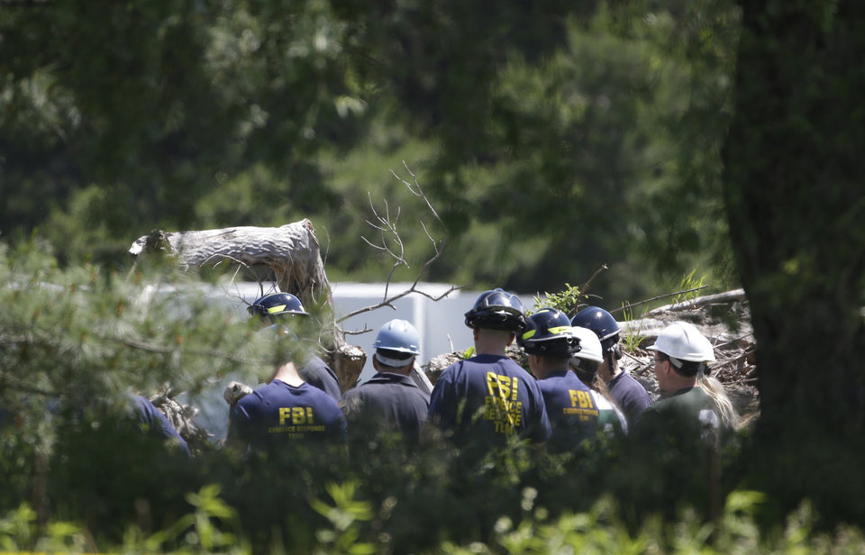 Photo - Members of the FBI evidence response team look over an area being cleared in Oakland Township, Mich., Tuesday, June 18, 2013 where officials continue the search for the remains of Teamsters union president Jimmy Hoffa, who disappeared from a Detroit-area restaurant in 1975. (AP Photo/Carlos Osorio)