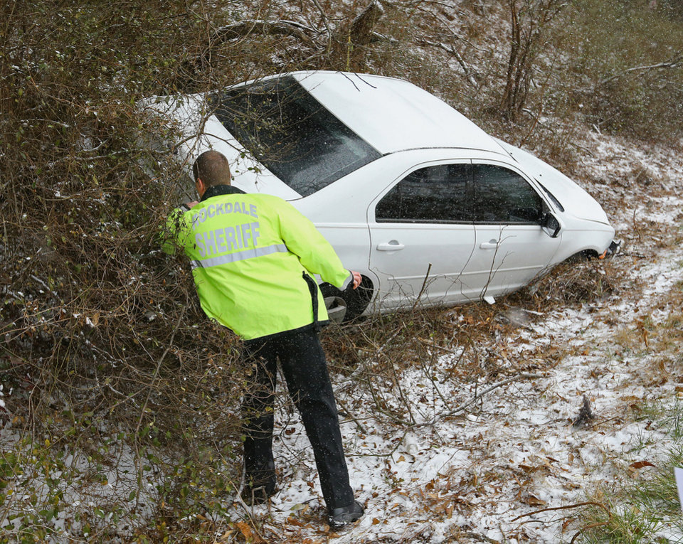 Photo - A Rockdale Sheriff deputy checks on a crashed vehicle off Interstate 20 West near Conyers, Ga., Tuesday, Jan. 28, 2014. A winter storm that would probably be no big deal in the North all but paralyzed the Deep South on Tuesday, bringing snow, ice and teeth-chattering cold, with temperatures in the teens in some places. (AP Photo/Atlanta Journal-Constitution, Curtis Compton)