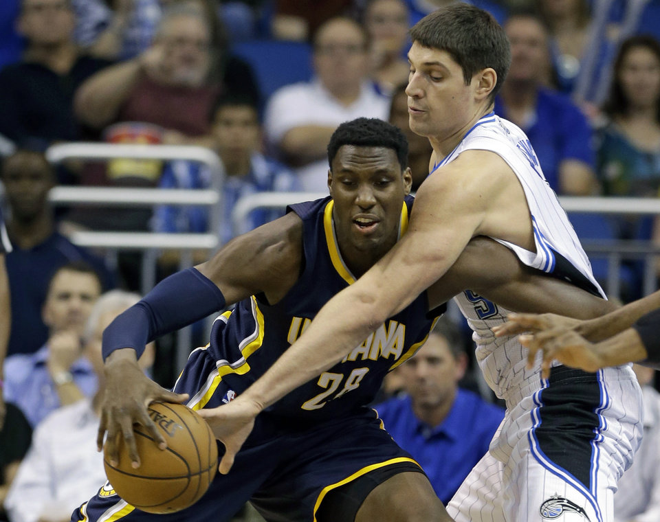 Indiana Pacers' Ian Mahinmi, left, of France, drives against Orlando Magic's Nikola Vucevic, of Montenegro,during the first half of an NBA basketball game, Wednesday, Jan. 16, 2013, in Orlando, Fla. (AP Photo/John Raoux)