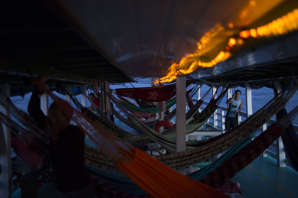"""Photo - In this May 22, 2014, photo, hammocks hang in the  """"Almirante Barbosa"""" regional boat, as it travels on the Solimoes river near Manaus, Brazil. Travelers without hammocks will have a hard time finding a place to sit on the boat, and competition for on-board real estate can be fierce. On the often-overcrowded ships, hammocks are hung from the overhead wooden beams and stacked two- or even three-high bunk bed-style, with adults on the lower levels and kids above.(AP Photo/Felipe Dana)"""