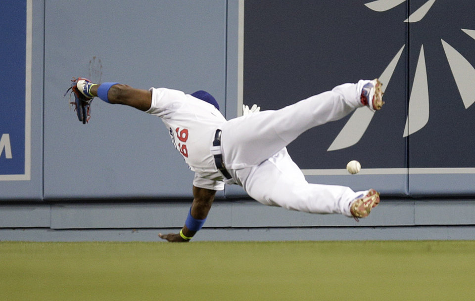 Photo - Los Angeles Dodgers right fielder Yasiel Puig can't make the catch on a two-run double by Philadelphia Phillies' Marlon Byrd during the fifth inning of a baseball game Thursday, April 24, 2014, in Los Angeles. (AP Photo/Jae C. Hong)