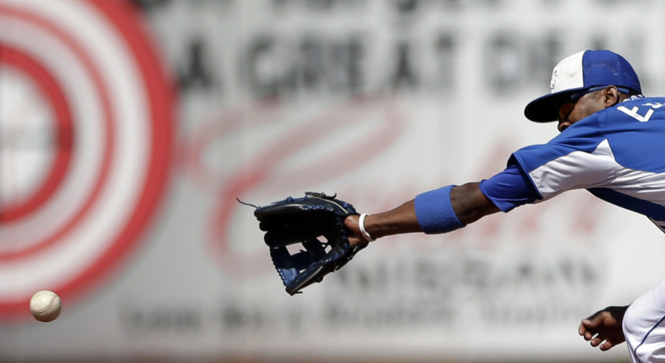 Photo - Kansas City Royals shortstop Alcides Escobar cannot reach a ball that went for a single by Colorado Rockies' Eric Young Jr. during the fourth inning in an exhibition spring training baseball game Tuesday, March 19, 2013, in Surprise, Ariz. (AP Photo/Gregory Bull)