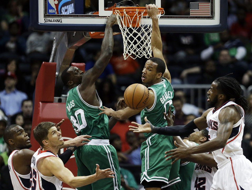 Photo - Boston Celtics' Brandon Bass and Avery Bradley, center left and right, watch a rebound fall into the hands of Atlanta Hawks' DeMarre Carroll, right, as teammates Paul Millsap, left, and Kyle Korver look on in the second quarter of an NBA basketball game, Wednesday, April 9, 2014, in Atlanta. (AP Photo/David Goldman)