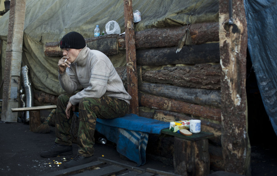 Photo - A member of a self defense volunteer group smokes a cigarette as he sits outside a tent in Kiev's Independence Square, Ukraine, Tuesday, March 11, 2014. (AP Photo/David Azia)
