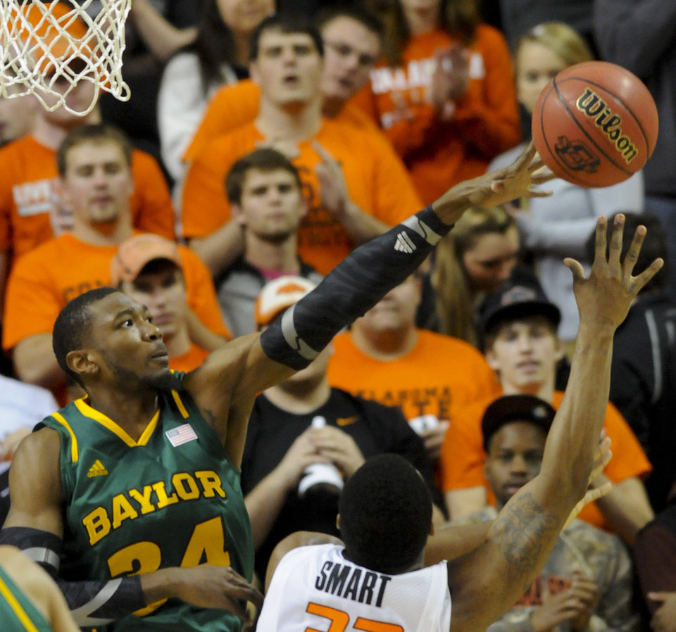 Baylor forward Cory Jefferson, left, deflects a shot over Oklahoma State guard Marcus Smart during the first half of an NCAA college basketball game in Stillwater, Okla., Wednesday, Feb. 6, 2013. (AP Photo/Brody Schmidt)