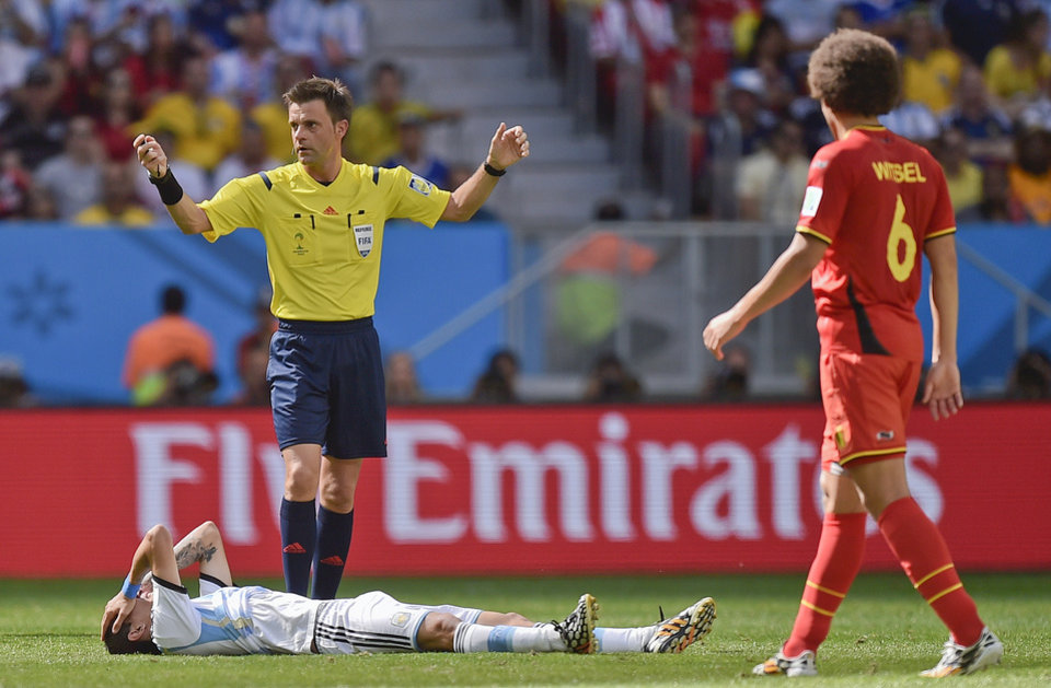 Photo - Referee Nicola Rizzoli of Italy stands over the injured Argentina's Angel di Maria during the World Cup quarterfinal soccer match between Argentina and Belgium at the Estadio Nacional in Brasilia, Brazil, Saturday, July 5, 2014. (AP Photo/Martin Meissner)