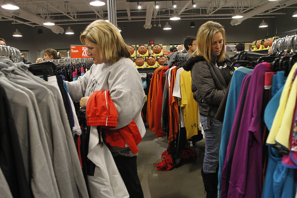 Photo - Amy Jones, of El Reno, and Sabrina Brown, of Mcloud, shop at Under Armour during Black Friday at The Outlet Shoppes at Oklahoma City, Thursday, Nov. 24, 2011.  Photo by Garett Fisbeck, For The Oklahoman