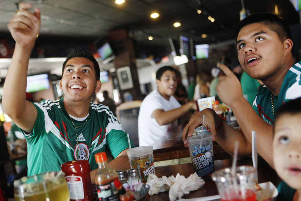 Photo -  Oscar Chavez, left, and Edgar Chavez, right, cheer on Mexico's national soccer team Tuesday during a World Cup watch party for the Brazil versus Mexico game at Medio Tiempo Sports Cantina and Grill. Photo by K.T. King, The Oklahoman   KT King -