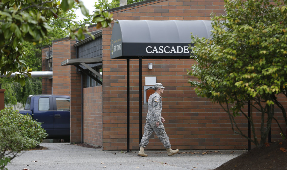 Photo - A solider walks Wednesday, June 5, 2013, outside the building housing the military courtroom where U.S. Army Staff Sgt. Robert Bales was taking part in a plea hearing at Joint Base Lewis-McChord in Washington state. Bales is accused of 16 counts of premeditated murder and six counts of attempted murder for a pre-dawn attack on two villages in Kandahar Province in Afghanistan in March, 2012. (AP Photo/Ted S. Warren)