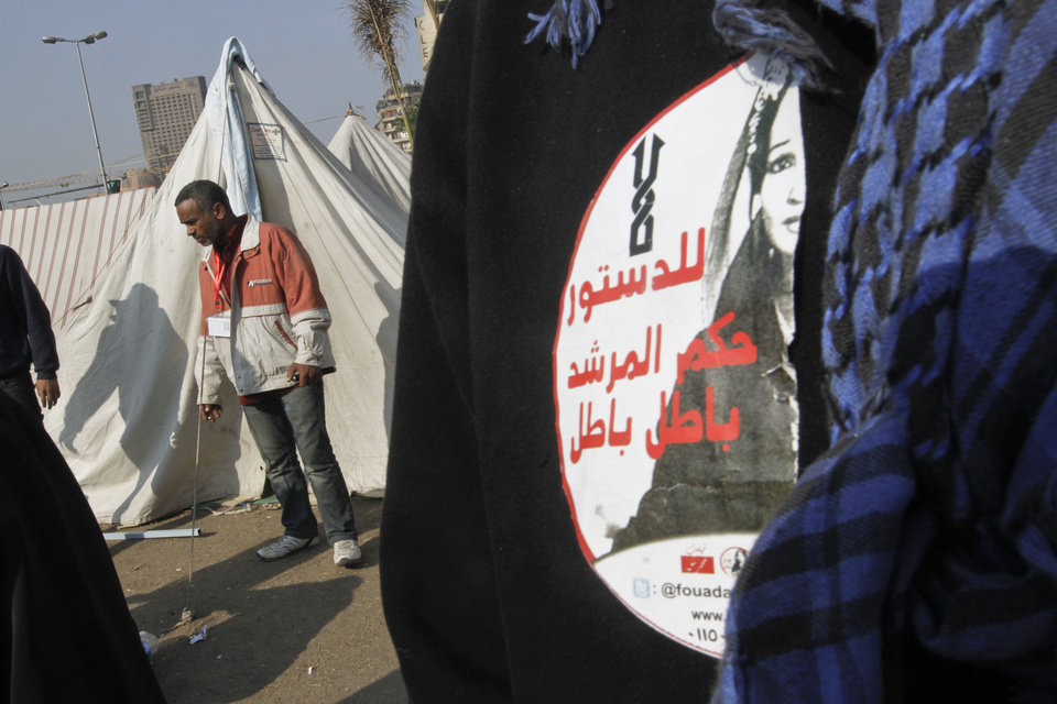 "A protesters wears a sticker with Arabic that reads, ""no to the supreme guide's rule, void, void,"" in Tahrir Square, the focal point of the Egyptian uprising, in Cairo, Sunday, Dec.16, 2012. Key Egyptian rights groups called Sunday for a repeat of the first round of the constitutional referendum, alleging the vote was marred by widespread violations. Islamists who back the disputed charter claimed they were in the lead with a majority of ""yes"" votes. (AP Photo/Amr Nabil)"