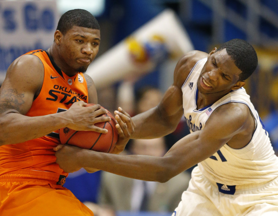 Photo - Oklahoma State guard Marcus Smart (33) and Kansas center Joel Embiid (21) battle to a jump ball during the second half of an NCAA college basketball game at Allen Fieldhouse in Lawrence, Kan., Saturday, Jan. 18, 2014. Kansas defeated Oklahoma State 80-78. (AP Photo/Orlin Wagner)