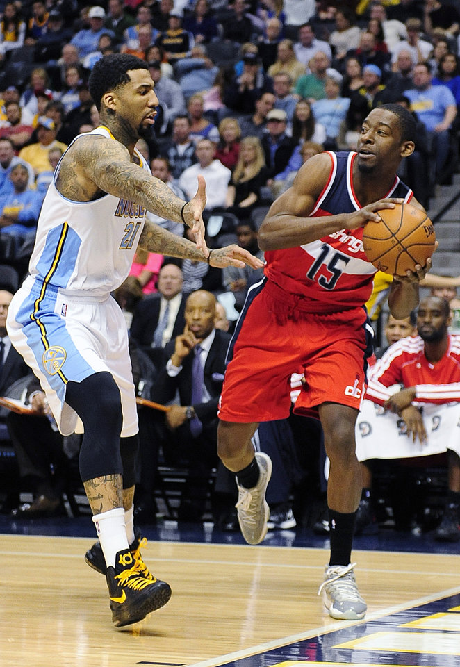 Denver Nuggets guard Wilson Chandler, left, guards Washington Wizards guard Jordan Crawford, right, in the first quarter of an NBA basketball game on Friday, Jan. 18, 2013, in Denver.  (AP Photo/Chris Schneider)