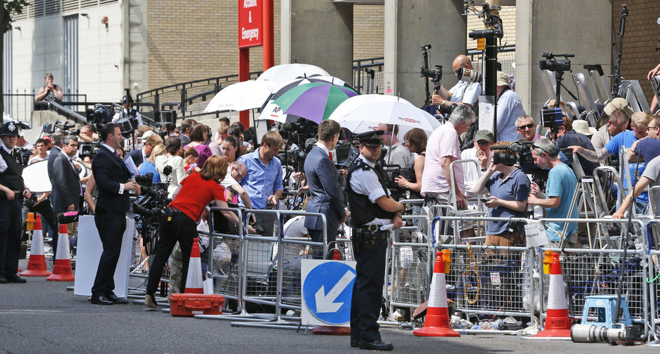 Photo - A British police officer, backdropped by members of the media, stands outside St. Mary's Hospital exclusive Lindo Wing in London, Monday, July 22, 2013. Buckingham Palace officials say Prince William's wife, Kate, has been admitted to the hospital in the early stages of labour.  Royal officials said that Kate traveled by car to St. Mary's Hospital in central London. Kate _ also known as the Duchess of Cambridge _ is expected to give birth in the private Lindo Wing of the hospital, where Princess Diana gave birth to William and his younger brother, Prince Harry.The baby will be third in line for the British throne _ behind Prince Charles and William _ and is anticipated eventually to become king or queen.(AP Photo/Lefteris Pitarakis)