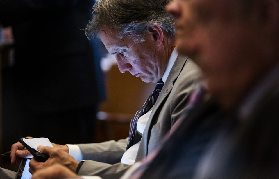 Photo - Attorney General Mike Hunter takes notes as he listens to the opening statements from the defense during opioid trial at the Cleveland County Courthouse in Norman, Okla. on Tuesday, May 28, 2019. The proceeding are the first public trial to emerge from roughly 2,000 U.S. lawsuits aimed at holding drug companies accountable for the nationÕs opioid crisis.   [Chris Landsberger/The Oklahoman]