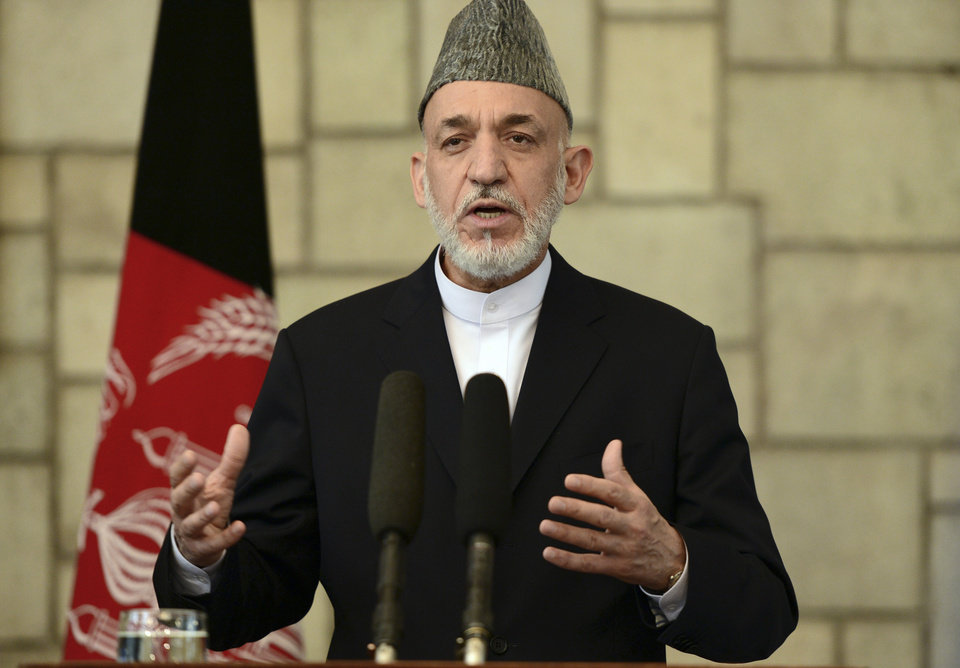 Photo - Afghan President Hamid Karzai talks during a joint press conference with British Prime Minister David Cameron at the presidential palace in Kabul, Afghanistan, Saturday, June 29, 2013. Karzai urged Taliban militants to sit down at the negotiating table, saying Saturday his government is still willing to start peace talks with the insurgents despite an attack by the group on the presidential palace this week. (AP Photo/Massoud Hossaini, Pool)