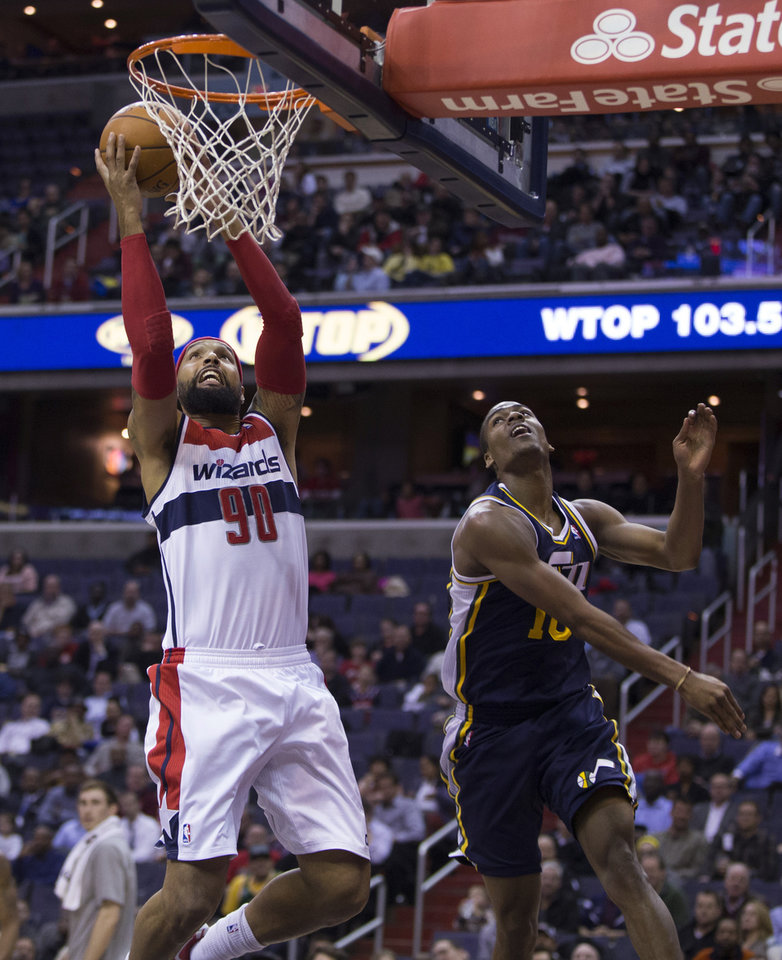 Photo - Washington Wizards power forward Drew Gooden (90) scores past Utah Jazz point guard Alec Burks during the first half of an NBA basketball game on Wednesday, March 5, 2014, in Washington. The Wizards defeated the Jazz 104-91. (AP Photo/ Evan Vucci)