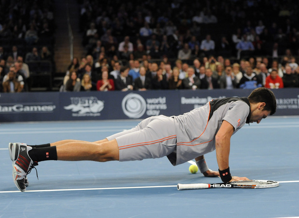 Photo - Novak Djokovic performs a push up on the court during play against Andy Murray in the BNP Paribas Showdown Tennis Tournament on Monday, March 3, 2014, in New York. Djokovic won 6-3, 7-6. (AP Photo/Kathy Kmonicek)