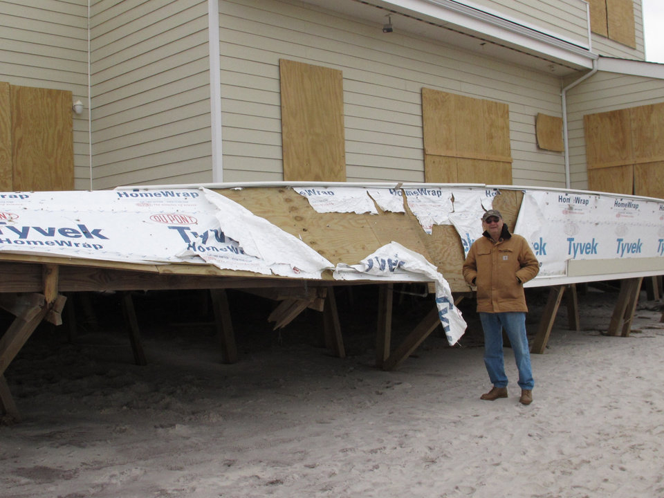 Photo -   In this Friday, Nov. 16, 2012 photo, homeowner Hyman Portnoy stands outside the damaged deck of his home in Ocean Beach, N.Y. The home was among hundreds destroyed or damaged on Fire Island during Superstorm Sandy. (AP Photo/Frank Eltman)