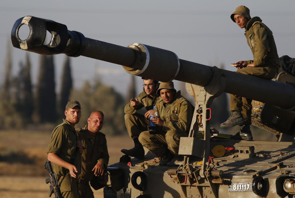 Photo - Israeli soldiers gather for a break on a mobile artillery unit at a position on the Israel-Gaza border, Friday, July 11, 2014. Gaza rocket fire struck a gas station and set it ablaze Friday in southern Israel, seriously wounding one person as rocket fire also came from Lebanon for the first time in the four-day-long offensive. Rocket fire by Palestinian militants continued from Gaza toward various locations in southern Israel. (AP Photo/Lefteris Pitarakis)