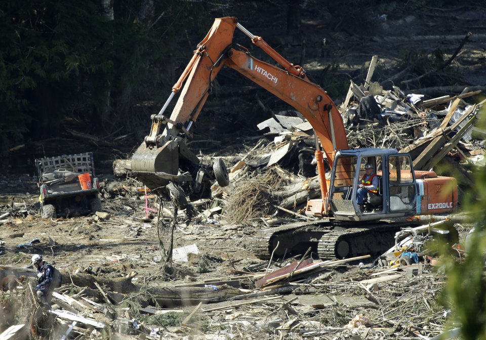 Photo - A piece of heavy equipment carries a mangled vehicle Tuesday, April 1, 2014, near Darrington, Wash., at the site of the deadly mudslide that hit the community of Oso,Wash. on March 22, 2014. Good weather and falling water levels aided the search for victims Tuesday. (AP Photo/Ted S. Warren)
