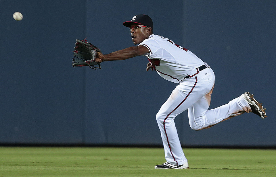 Photo - Atlanta Braves center fielder B.J. Upton runs down a fly ball from Miami Marlins' Casey McGehee  in the eighth inning of a baseball game on Thursday, July 24, 2014, in Atlanta. (AP Photo)