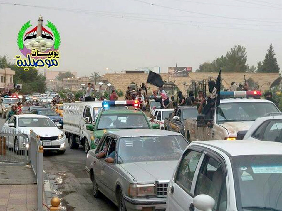 Photo - In this still image posted on a militant Twitter account on Wednesday, June 11, 2014, which has been authenticated based on its contents and other AP reporting, militants wave the black flag used by the al-Qaida-inspired Islamic State of Iraq and the Levant (ISIL) as they parade down a main road in Mosul, Iraq in captured Iraqi Army and Police vehicles.  Iraqi officials say al-Qaida-inspired militants who this week seized much of the country's Sunni heartland have pushed into an ethnically mixed province northeast of Baghdad, capturing two towns there.(AP Photo/militant source via Twitter)