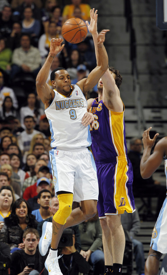Photo - Denver Nuggets forward Andre Iguodala (9) passes the ball as Los Angeles Lakers forward Pau Gasol, of Spain, defends in the first quarter of an NBA basketball game in Denver, Wednesday, Dec. 26, 2012. (AP Photo/David Zalubowski)