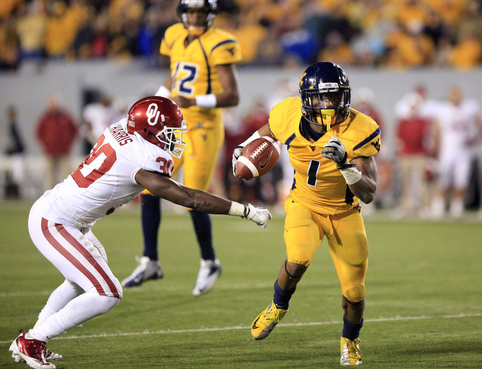 West Virginia wide receiver Tavon Austin (1) slips past Oklahoma\'s Javon Harris (30) for a rushing touchdown during the third quarter of their NCAA college football game against Oklahoma in Morgantown, W.Va., on Saturday, Nov. 17, 2012. Oklahoma won 50-49. (AP Photo/Christopher Jackson)